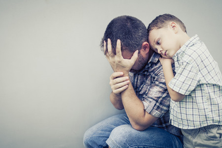 Photo pour sad son hugging his dad near wall at the day time - image libre de droit