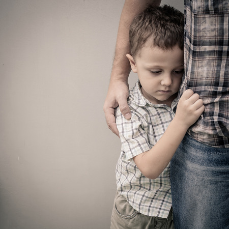 Photo for sad son hugging his dad near wall at the day time - Royalty Free Image