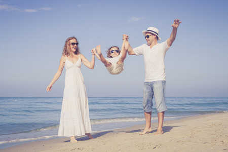 Foto de Happy family walking on the beach at the day time. Concept of friendly family. - Imagen libre de derechos