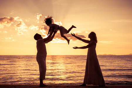 Photo for Silhouette of happy family who playing on the beach at the sunset time. Concept of friendly family. - Royalty Free Image