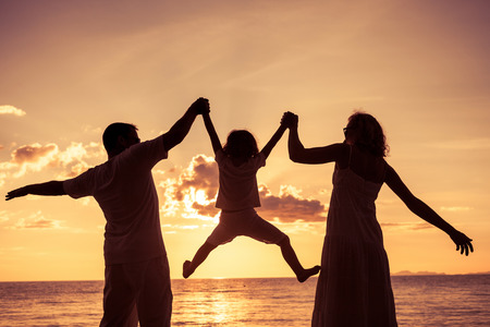 Photo pour Silhouette of happy family who playing on the beach at the sunset time. Concept of friendly family. - image libre de droit