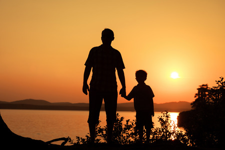 Foto de father and son playing on the coast of lake in the mountains of at the sunset time - Imagen libre de derechos