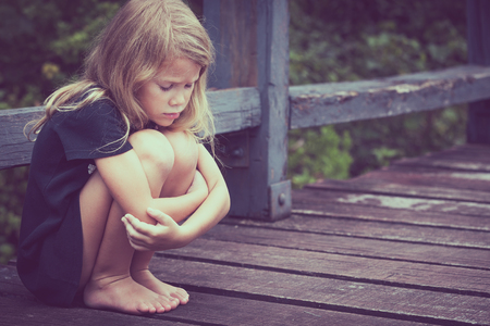 Foto de Portrait of sad blond little girl sitting on the bridge at the day time - Imagen libre de derechos
