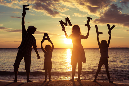 Happy family standing on the beach at the sunset time. They keep the letters forming the word  family. Concept of friendly family.