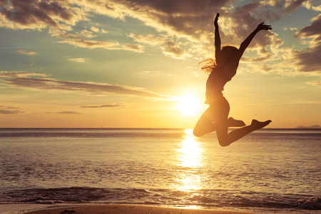 Photo for Happy teen girl  jumping on the beach at the sunset time - Royalty Free Image