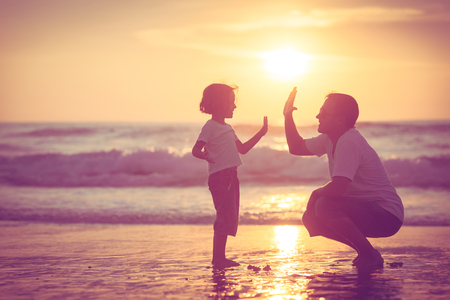 Foto de Father and son playing on the beach at the sunset time. Concept of friendly family. - Imagen libre de derechos