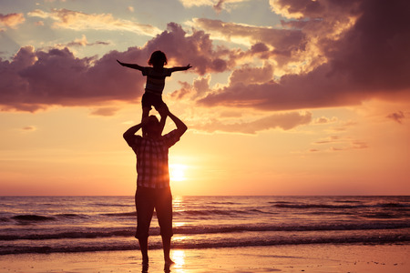 Photo pour Father and son playing on the beach at the sunset time. Concept of friendly family. - image libre de droit