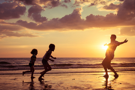 Photo for Father and children playing on the beach at the sunset time. Concept of friendly family. - Royalty Free Image