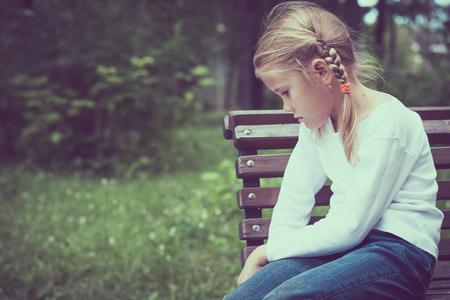 Foto de Portrait of sad little girl at the day time. - Imagen libre de derechos
