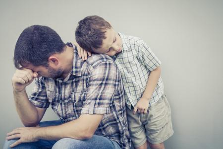 Foto de sad son hugging his dad near wall of house at the day time - Imagen libre de derechos