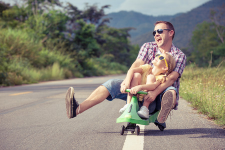 Foto de Father and daughter playing  on the road at the day time.  Concept of friendly family. - Imagen libre de derechos