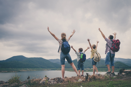 Photo pour Happy family standing near the lake at the day time.  Concept of friendly family. - image libre de droit