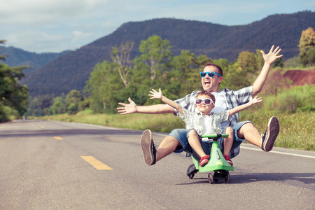 Foto de Father and son playing  on the road at the day time.  Concept of friendly family. - Imagen libre de derechos