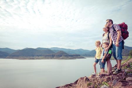 Foto de Happy family standing near the lake at the day time.  Concept of friendly family. - Imagen libre de derechos