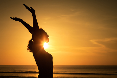 Photo pour woman open arms under the sunset at sea. Concept of healthy life. - image libre de droit