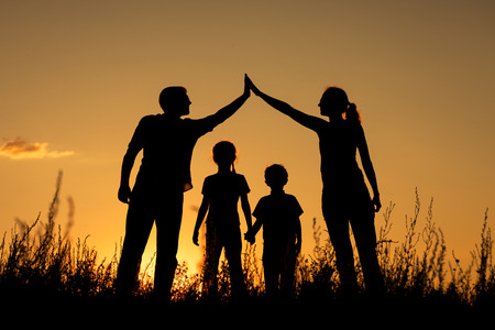 Foto de Happy family standing in the park at the sunset time.  Concept of friendly family. - Imagen libre de derechos
