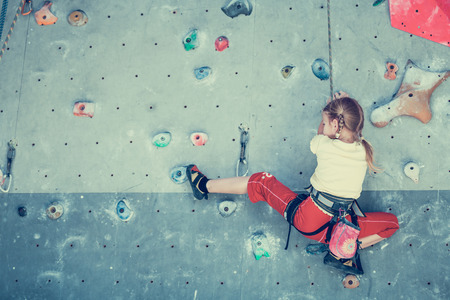 Photo pour little girl climbing a rock wall indoor - image libre de droit