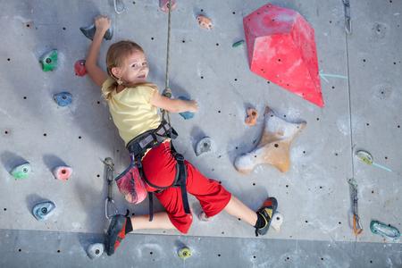 Foto de little girl climbing a rock wall indoor - Imagen libre de derechos