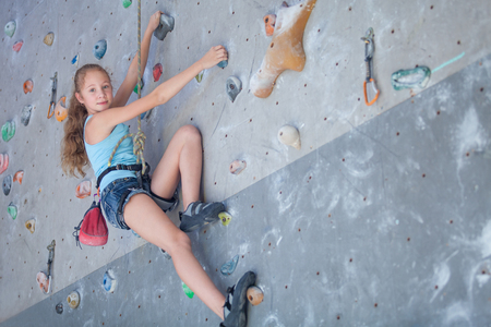 Photo pour teenager climbing a rock wall indoor - image libre de droit