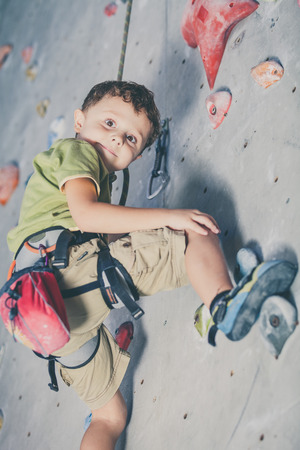 Photo pour little boy climbing a rock wall indoor - image libre de droit