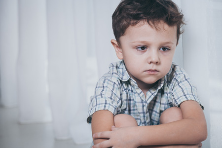 Foto de Portrait of sad little boy sitting near the window at home at the day time - Imagen libre de derechos