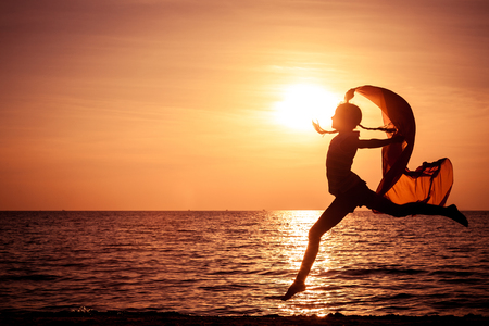 Foto de Happy girl jumping on the beach at the sunset time - Imagen libre de derechos