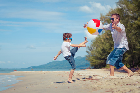 Foto de Father and son with ball playing soccer on the beach at the day time. Concept of friendly family. - Imagen libre de derechos