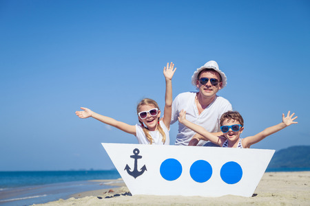 Photo pour Father and children playing on the beach at the day time. Concept of friendly family. - image libre de droit
