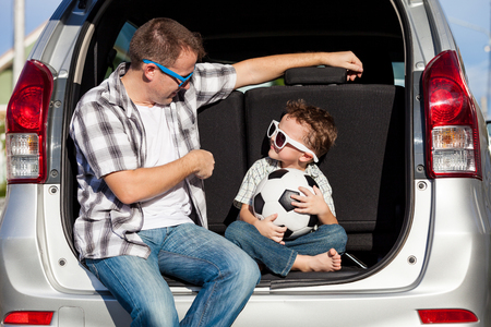 Foto de Happy father and son getting ready for road trip on a sunny day.  Concept of friendly family. - Imagen libre de derechos