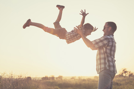Foto de Father and son playing in the park at the sunset time. People having fun on the field. Concept of friendly family and of summer vacation. - Imagen libre de derechos
