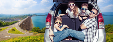 Photo pour Happy father and children sitting in the car at the sunny day. Concept of friendly family on vacation. - image libre de droit