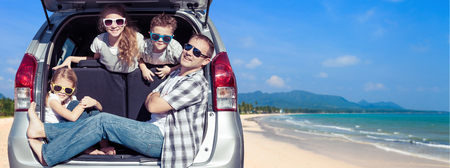 Photo pour Happy father and children sitting in the car at the sunny day. People having fun outdoors. Concept of friendly family on vacation. - image libre de droit