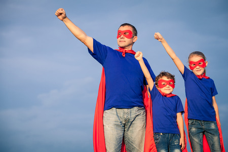 Photo for Father and children playing superhero at the day time. People having fun outdoors. Concept of friendly family. - Royalty Free Image