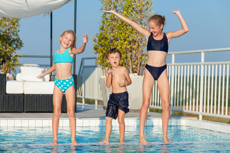 Foto de Three happy children playing near swimming pool at the day time.  People having fun outdoors. Concept of friendly family and  summer vacation. - Imagen libre de derechos