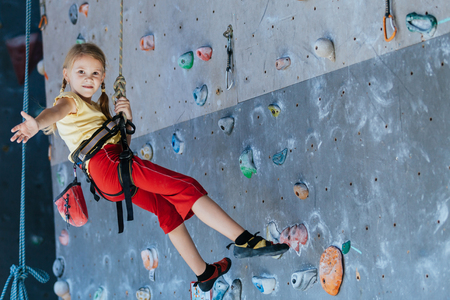 Foto per little girl climbing a rock wall indoor. Concept of sport life. - Immagine Royalty Free