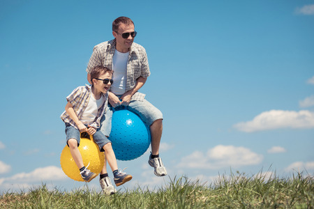 Photo for Father and son playing on the field at the day time. People having fun outdoors. They jumping on inflatable balls on the lawn. Concept of friendly family. - Royalty Free Image