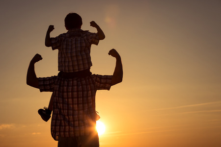 Foto de Father and son walking on the field at the sunset time. Concept of friendly family. - Imagen libre de derechos