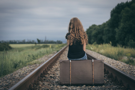 Foto de Portrait of young sad ten girl sitting with suitcase outdoors  on the railway at the day time. Concept of sorrow. - Imagen libre de derechos