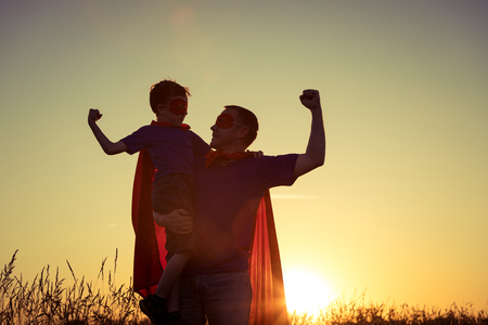 Foto de Father and son playing superhero at the sunset time. People having fun outdoors. Concept of friendly family. - Imagen libre de derechos