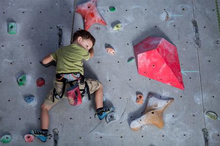 Foto de little boy climbing a rock wall indoor. Concept of sport life. - Imagen libre de derechos