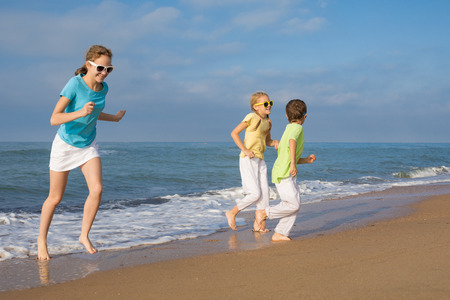 Three happy children running on the beach at the day time. People having fun outdoors. Concept of friendly family and of summer vacation.