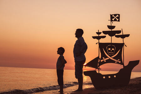 Foto de Father and son playing on the beach at the sunset time. They playing with a cardboard pirate ship. People having fun outdoors. Concept of summer vacation and friendly family. - Imagen libre de derechos