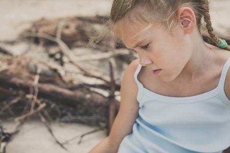 Foto de Portrait of one sad little girl. Child sitting on the beach at the day time. Concept of sorrow. - Imagen libre de derechos