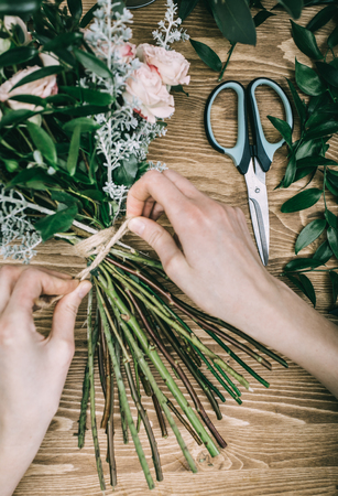 Photo for Crop shot from above of florist finishing floral composition banding green stems with craft string. - Royalty Free Image