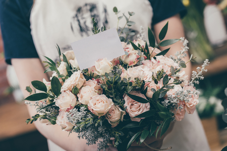 Photo for Faceless florist demonstrating tender bouquet with roses and blank congratulations card. - Royalty Free Image