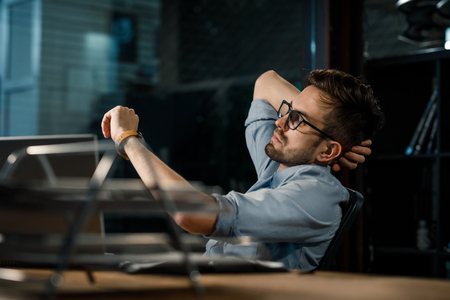 Foto de Man working late in office checking time - Imagen libre de derechos