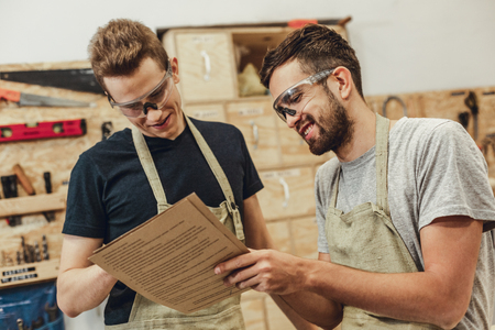 Foto de Two handsome young men in safety goggles cheerfully smiling and reading papers while working in joinery together - Imagen libre de derechos