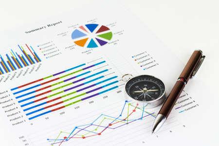 Foto de Bussiness graphs and finances with a compass lying nearby. - Imagen libre de derechos