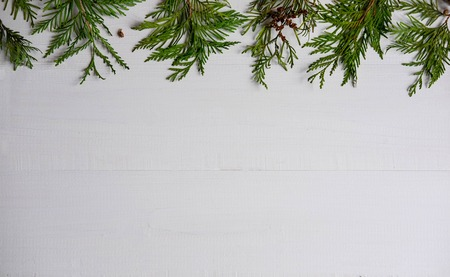 Photo pour Christmas composition with live branches of a coniferous tree. The form for the text of the New Year banner on a white wooden background. Collage with branches of natural needles. New Years composition - image libre de droit