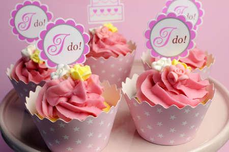 Foto de Pink wedding cupcakes with I Do topper signs on pink cake stand - close up. - Imagen libre de derechos
